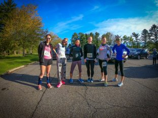 six women in running gear smiling on race course before race